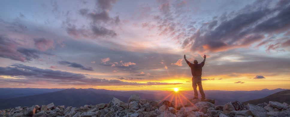 Man with raised arms overlooking beauitful sunrise